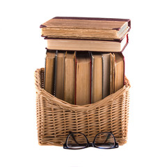 Stack of old antique books in a wicker basket and spectacles