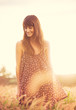 Romantic Model in Sun Dress in Golden Field at Sunset