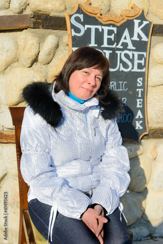 Brunette middle-aged woman in a stylish white jacket with fur ho