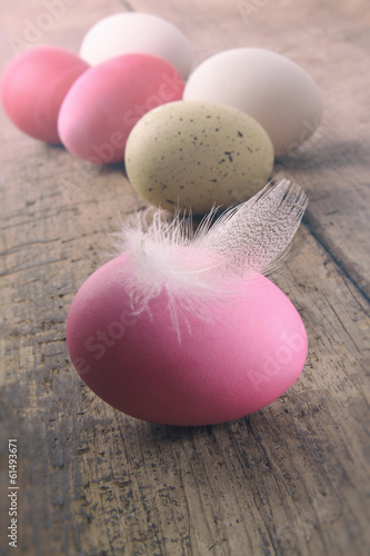 Easter eggs with feather on  wooden table