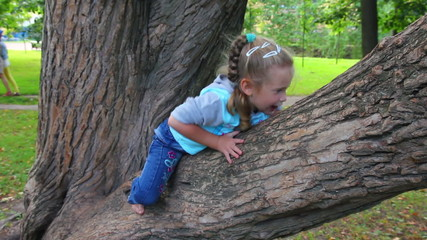 little girl climbs on tree