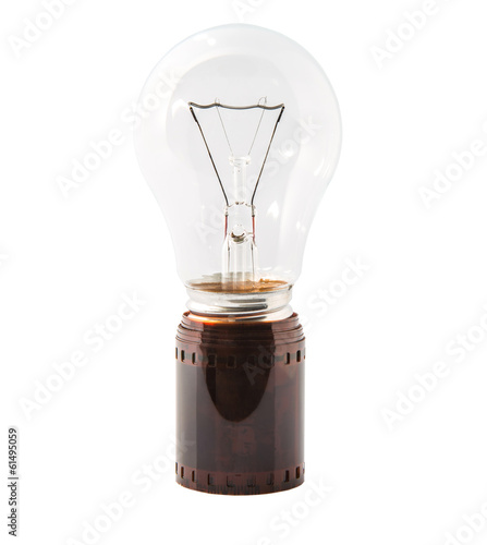 Light bulb and used photography film strip over white background