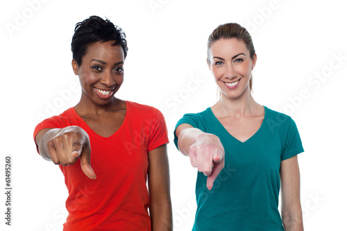 Smiling friends pointing to you