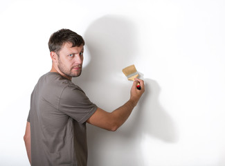 Man with a brush paints the withe wall