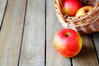 ripe apples and a basket on wooden background