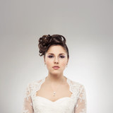 Young and beautiful bride over the grey background