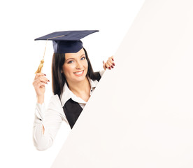 A happy graduate girl with a blank banner isolated on white