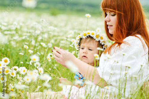 fun of little girl and redhead young woman in daisy field