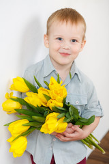 Portrait of a boy with a bouquet of yellow tulips on a white