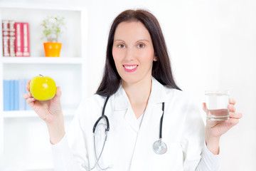 doctor holding and a glass of clear fresh water and an apple