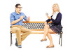 Young couple playing cards seated on wooden bench
