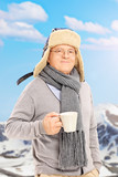 Senior man holding a cup in front of snowy mountain