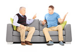 Two men arguing seated on a sofa