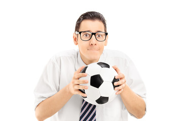 Young man holding a football and watching sports match