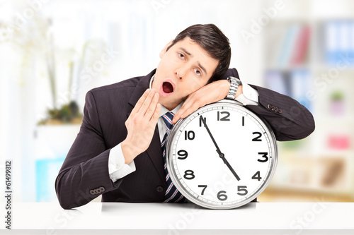 Sleepy young businessman leaning his head on a big wall clock