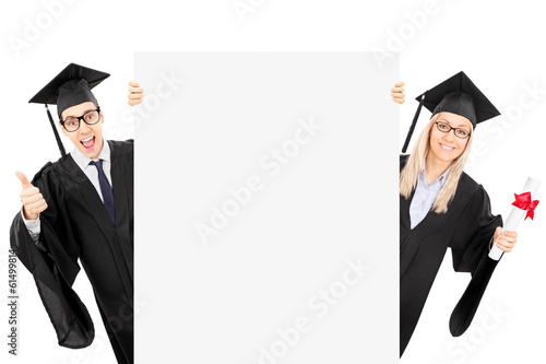 Two college students standing behind blank panel and gesturing