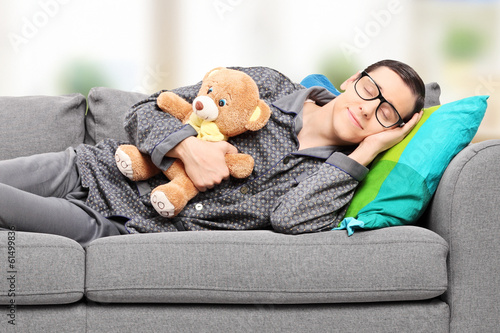 Young man in pajamas sleeping on sofa at home