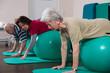 canvas print picture - Physiotherapeutin übt mit Senioren auf Bällen