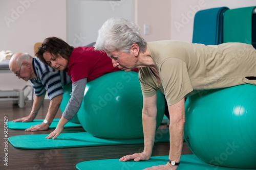 canvas print picture Physiotherapeutin übt mit Senioren auf Bällen