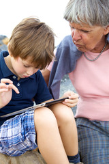 Child teaching grandmother how to use tablet