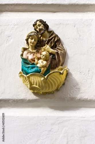 Religious icon of the Holy Family on stone wall.