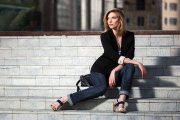 Young business woman sitting on the steps