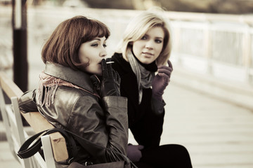 Two young women sitting on a bench