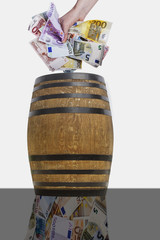 Hand throwing crumpled bills into the barrel