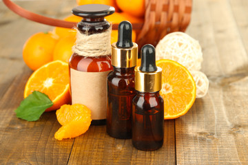 Tangerine essential oil and tangerines on wooden table