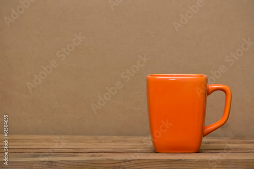 Orange mug on  wooden table