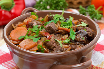 Stew with beef, vegetables and prunes in a saucepan, close-up