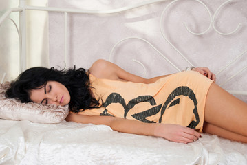 Beautiful brunette girl sleeping on the bed