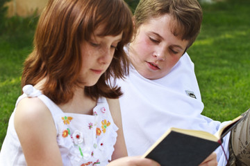 Teen.Portrait of cute kids reading books  in natural environment