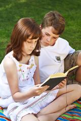 Teenagers.Portrait of cute kids reading books  in natural enviro