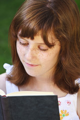 Relaxation.Young beautiful girl reading a book outdoor