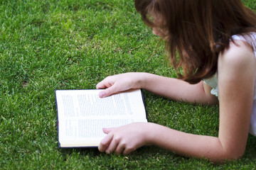Tale.Young beautiful girl reading a book outdoor