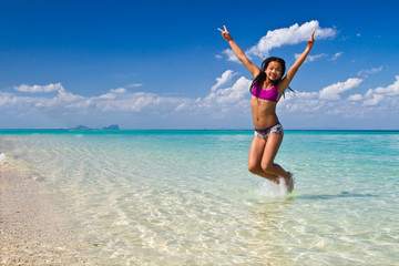 Girl jumping in the water at the beach of the Koh Ngai island Th