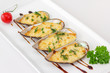 Baked Mussels under Cream Cheese Sauce, garnished with dill and