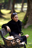 Beautiful Asian lady in black dress, posing in the park, greener