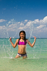 Girl splashing in the water at the beach of the Koh Ngai island