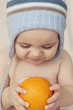 Cute little baby sitting on the bed  holding an orange