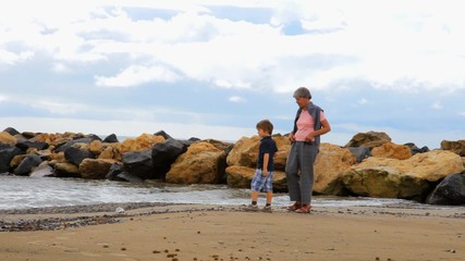 Grandmother and grandson playing on the beach