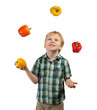Little boy juggles some fruits and vegetables