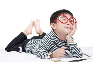 Smart child lying on bed  writing and thinking