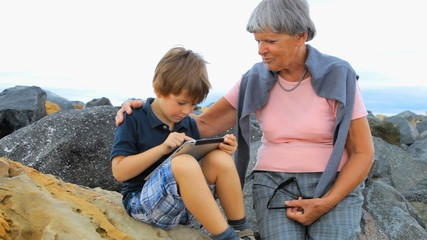 Happy kid playing with tablet with grandmother