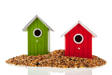 Green and red bird houses with seed