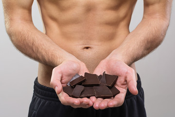 Young fit man holding dark chocolate pieces