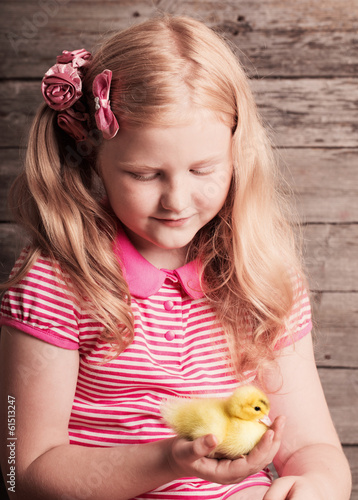 girl with gosling on wooden background