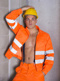 Young construction worker with orange suit open on naked torso