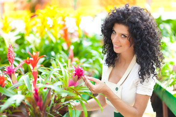 Woman looking at the flowers in a green house